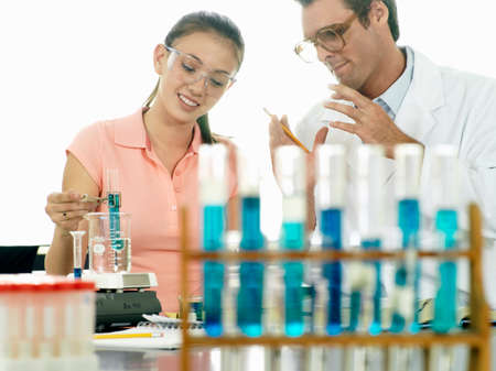 profile measurement: Teenage girl (15-17) doing science experiment at desk in classroom, teacher assisting, smiling