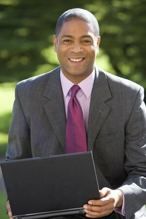 only one mid adult man: Businessman with laptop computer, smiling, portrait