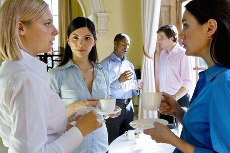 Businesswomen with teacups in conversation, businessmen in background