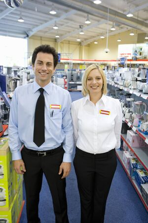 store clerk: Young salesman and woman in electronics aisle, smiling, porttrait