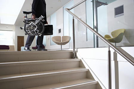 low section view: Businessman carrying commuter bicycle and briefcase up steps in lobby, low section, side view