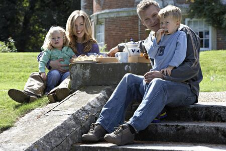 two generation family: Two generation family sitting on steps in garden, having tea and sandwiches, smiling, portrait