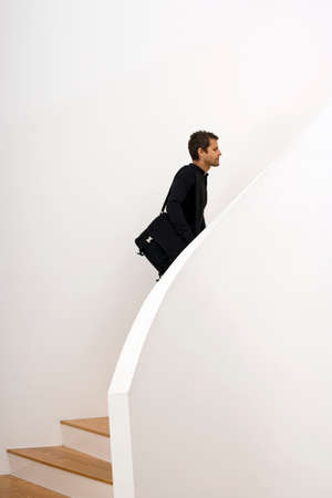 one mid adult man only: Man ascending staircase, carrying shoulder bag, profile LANG_EVOIMAGES