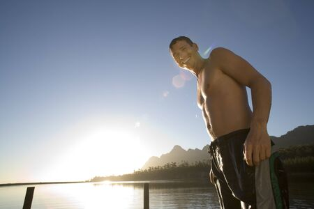 swimming shorts: Man, in swimming shorts, standing on lake jetty at sunset, smiling, portrait, low angle view (lens flare, backlit)
