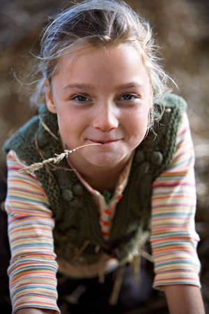 Girl (9-11) with piece of straw in mouth, smiling, close-up, front view, portrait
