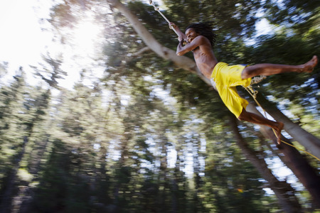 swimming shorts: Boy (8-10), in yellow swimming shorts, swinging on rope above lake, low angle view (backlit) LANG_EVOIMAGES