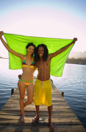 holding aloft: Couple standing on lake jetty, arms around each other, holding aloft green towel, smiling, front view, portrait LANG_EVOIMAGES