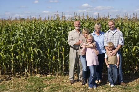 Familie van drie generaties door maïsveld, glimlachen, portret