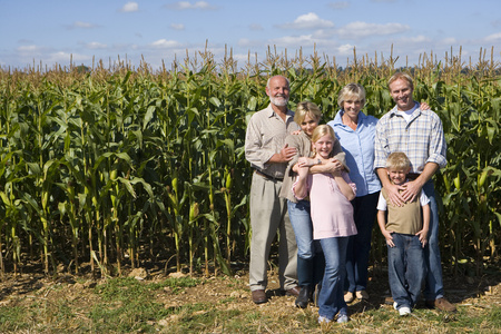 Family of three generations by corn field, smiling, portrait