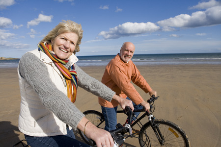 Senior couple cycling on beach, smiling, portrait, side view Imagens