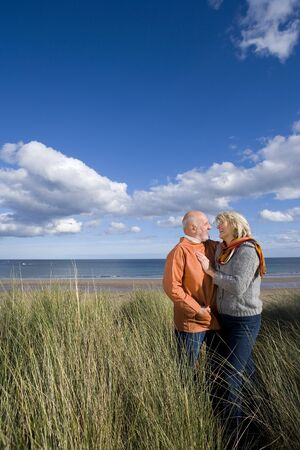 to the other side: Senior couple arm in arm on sand dune, smiling at each other, side view