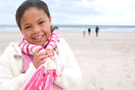 scarf beach: Girl (7-9) on beach, hands on scarf, family in background, smiling, portrait LANG_EVOIMAGES