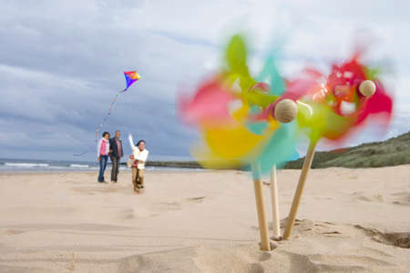 pinwheels: Pinwheels on beach, family with kite in background (blurred motion)