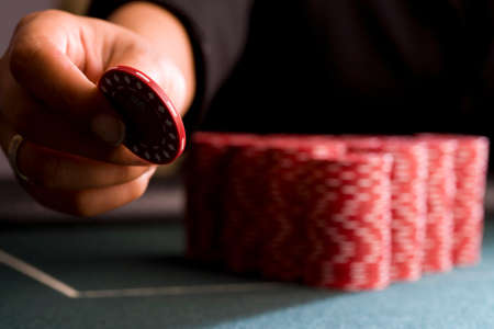 high stakes: Woman placing gambling chip on table, close-up