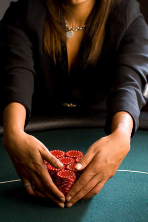 high stakes: Woman collecting piles of gambling chips on table, mid section