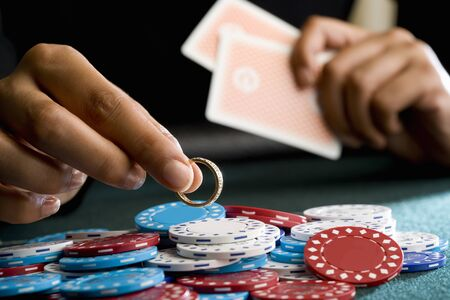 high stakes: Woman placing ring on pile of gambling chips on table, mid section LANG_EVOIMAGES
