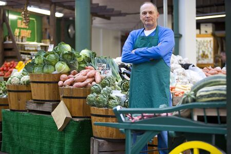 grocer: Green grocer with arms crossed by produce, portrait