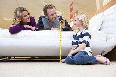 Young couple measuring bed in furniture shop, smiling at daughter (6-8)