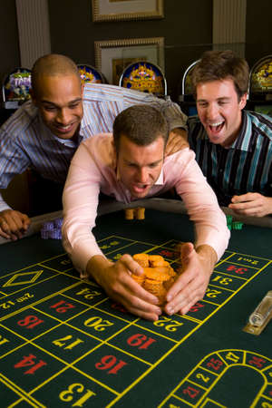 roulette table: Young man with friends collecting pile of gambling chips from roulette table in casino, smiling