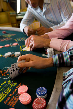 concealing: Young men gambling at poker table in casino, section LANG_EVOIMAGES