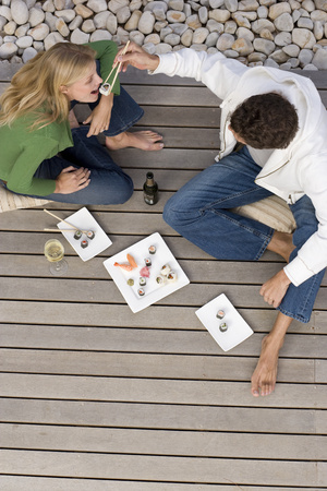 Young couple on decking, man feeding woman sushi with chopsticks, elevated view