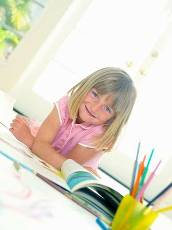 tilt: Girl (4-6) with book, smiling, portrait, low angle view (tilt)
