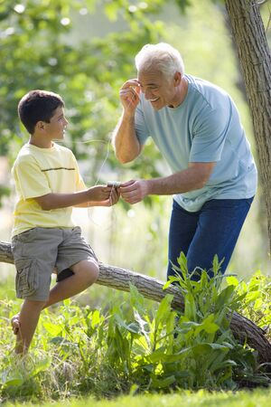 mp3 player: Boy (9-11) sharing MP3 player with grandfather outdoors