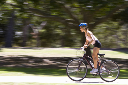 Young woman cycling in park, side view