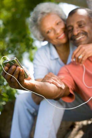 appreciating: Senior couple with MP3 player, smiling LANG_EVOIMAGES