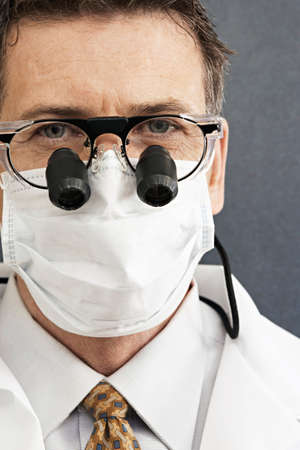 surgical mask: Male dentist wearing surgical mask and surgical loupes, close-up, front view, portrait