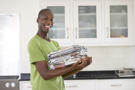 bundling: Young man with bundle of newspapers in kitchen, smiling, portrait