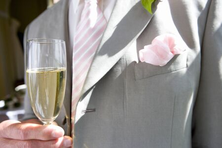 champagne flute: Groom holding champagne flute, close-up, mid section LANG_EVOIMAGES