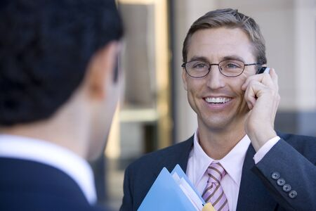 differential: Businessman in spectacles using mobile phone, smiling, close-up (differential focus)