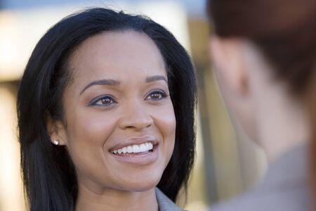 differential focus: Businesswoman talking to colleague, smiling, close-up (differential focus)