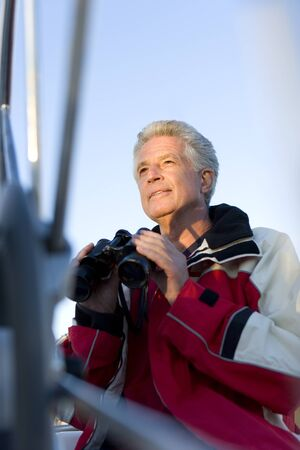 differential: Mature man, in red waterproof jacket, standing on deck of yacht, holding pair of binoculars, smiling, low angle view (differential focus)