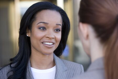 two person only: Businesswoman talking to colleague, smiling, close-up (differential focus)