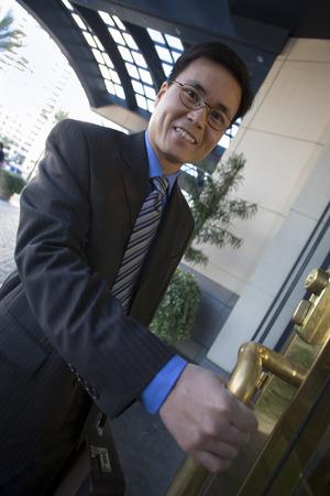 tilt view: Businessman entering building, opening door, smiling, side view, portrait (tilt)