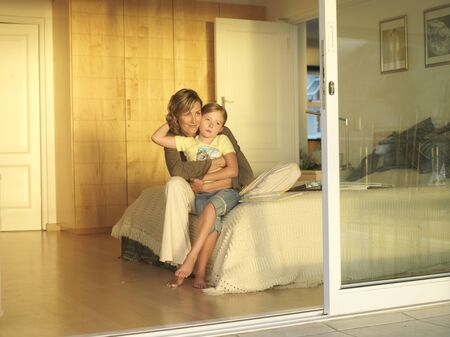 sliding doors: Mother and daughter (6-8) sitting on edge of double bed, view through open sliding doors LANG_EVOIMAGES