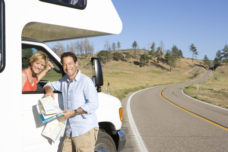 Couple with motor home, man with map, woman looking out of window, smiling, portrait
