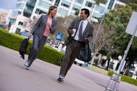 rucksacks: Businessman and businesswoman walking on pavement in city, carrying rucksacks, smiling (tilt) LANG_EVOIMAGES