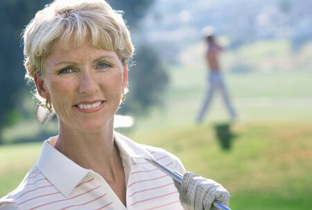 differential focus: Mature woman in striped polo shirt and golf glove standing on golf course, holding putter on shoulder, smiling, close-up, portrait (differential focus)