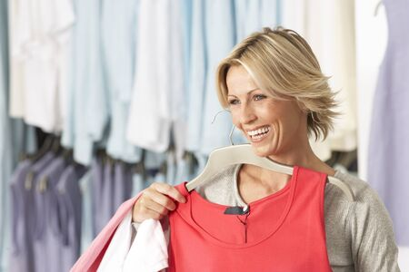 vest top: Mature blonde woman shopping in clothes shop, holding red vest top on coathanger, smiling