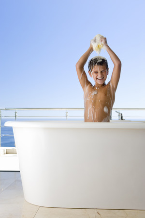 soaping: Boy (6-8) holding sponge above head in bubble bath, smiling, portrait