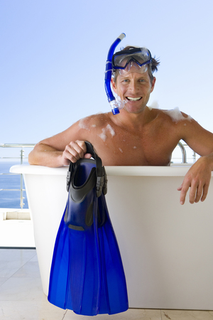 snorkle: Man wearing snorkle and holding flippers whilst in bubble bath, smiling, portrait LANG_EVOIMAGES