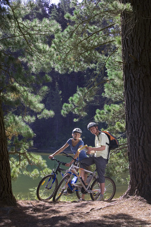 rucksacks: Young couple, with rucksacks, mountain biking along woodland trail beside lake, holding map, smiling, portrait LANG_EVOIMAGES