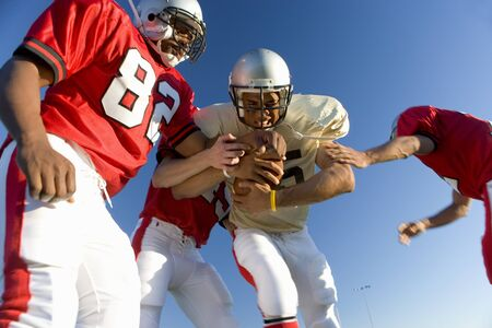 opposing: American football players tackling opposing player with ball, low angle view