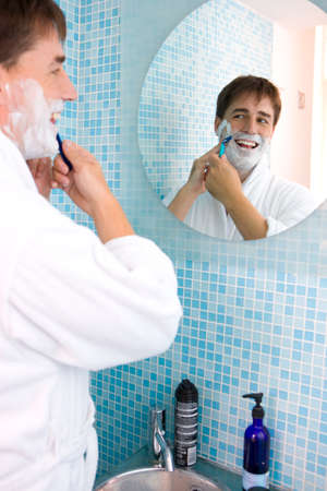 workday: Young man shaving in mirror LANG_EVOIMAGES