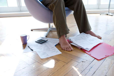paying bills online: Man with paperwork by feet, in armchair, low section