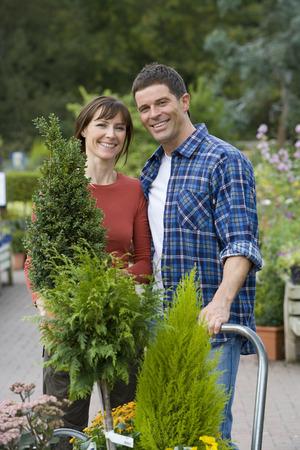 garden center: Couple with plants in garden center, smiling, portrait