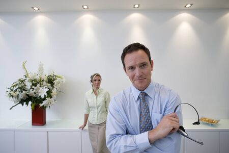 teleconference: Businessman and woman with headsets in conversation, smiling LANG_EVOIMAGES